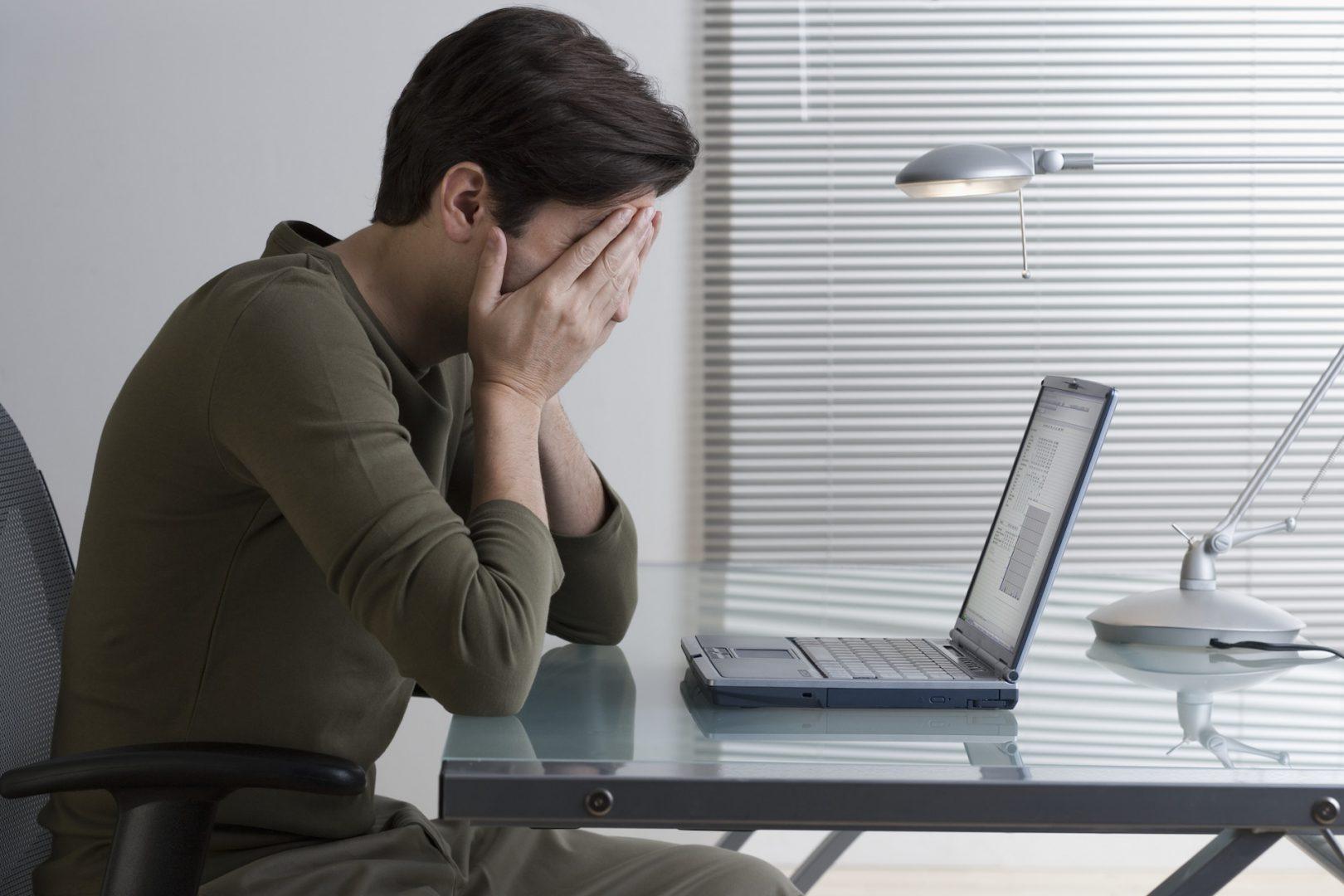 パソコンを前に悩んでいる人の写真