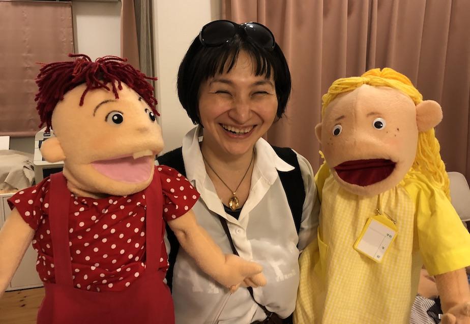 レッドくん人形とイエローちゃん人形を持つ佐藤安南