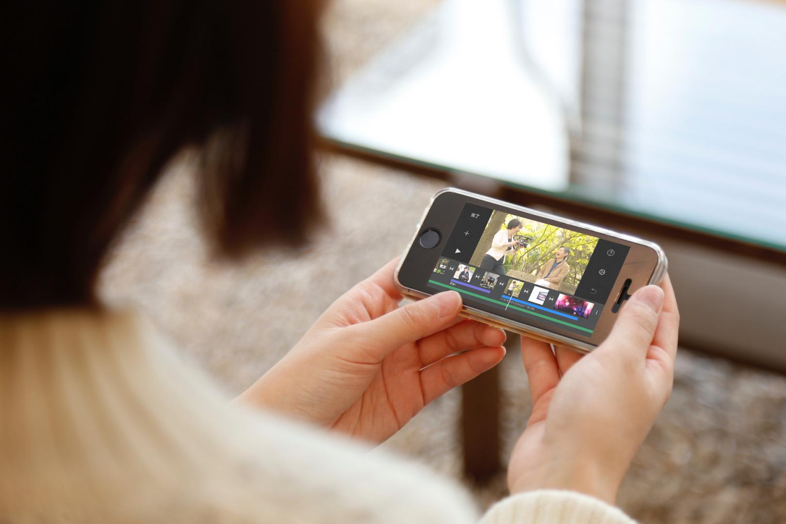 iPhoneでiMovieを使って動画編集する女性