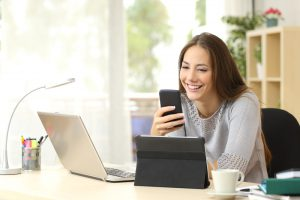 スマートフォンを見て微笑む外国人女性