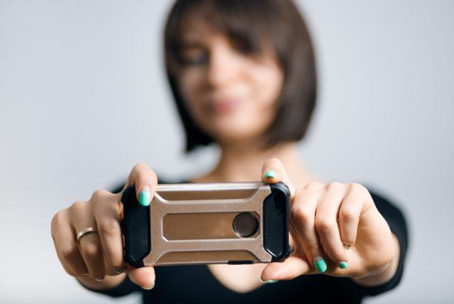 スマホを持って撮影している女性の正面写真
