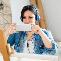 机の前でスマホを持って撮影している女性