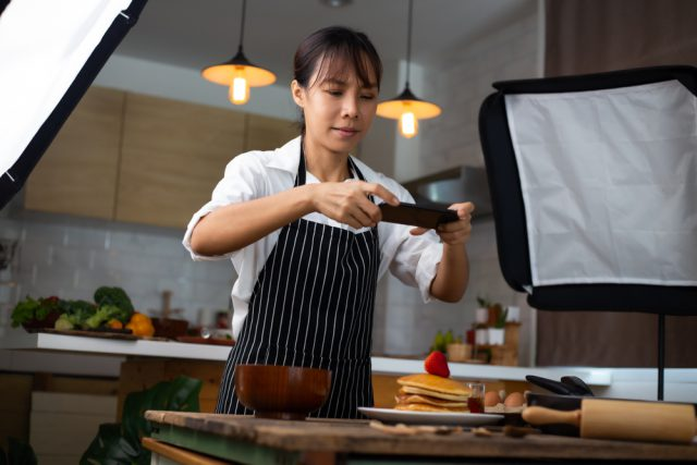 スマホで料理を撮影する女性の写真