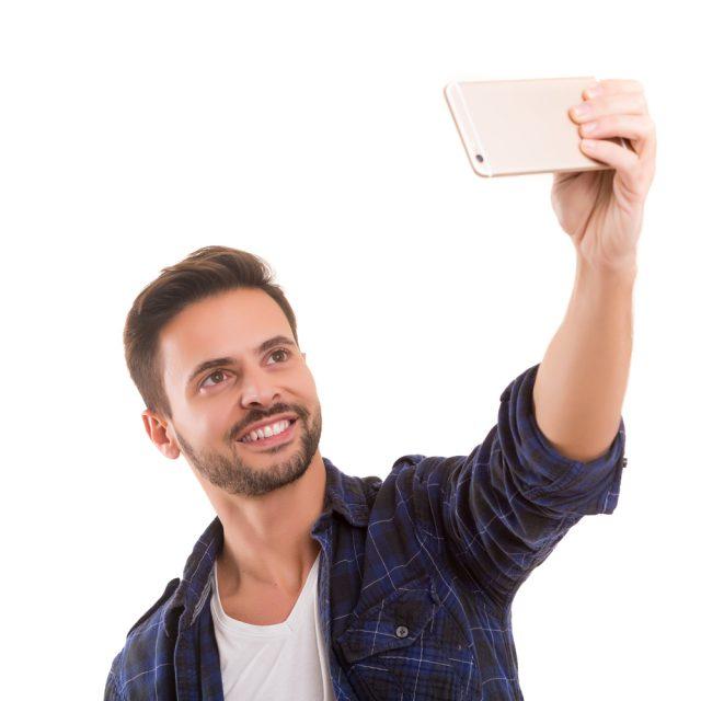 スマホを上に掲げて自撮りする欧米人男性の写真