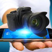 スマホの上に一眼レフカメラを載せて手のひらに置いている写真